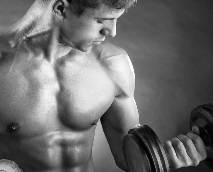 A man lifting dumbbells and flexing his biceps.