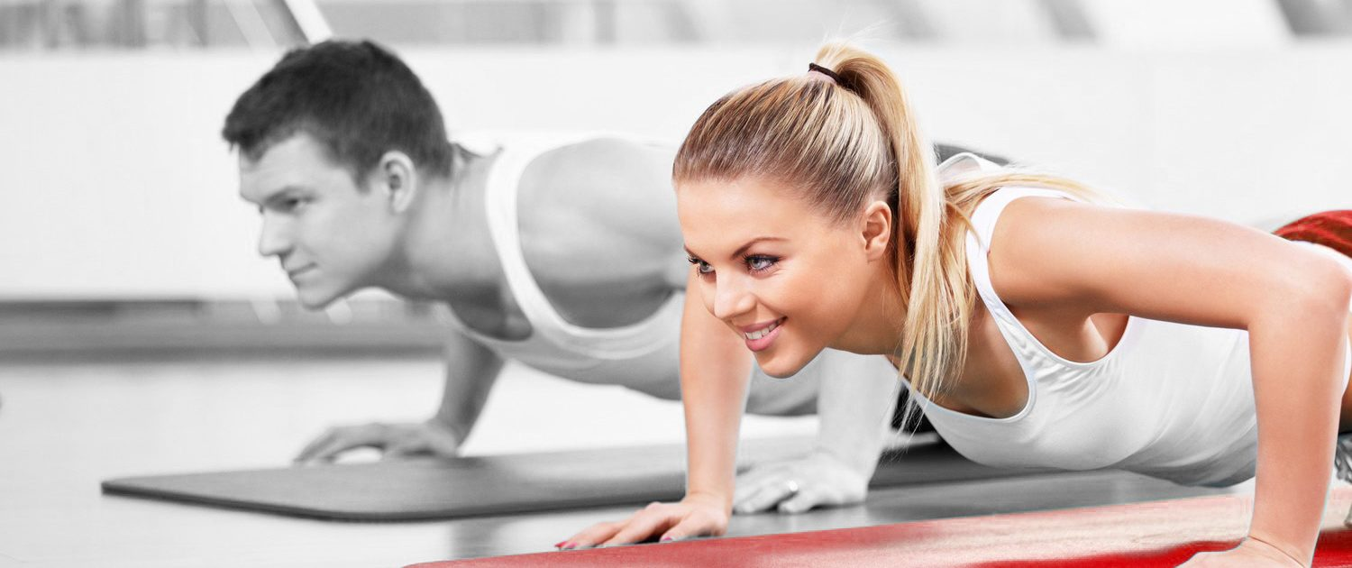 stock image of a lady have personal training using a red yoga mat.