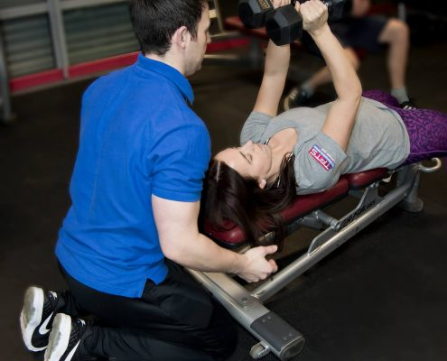 darren assisting his personal training client with dumbbell flys