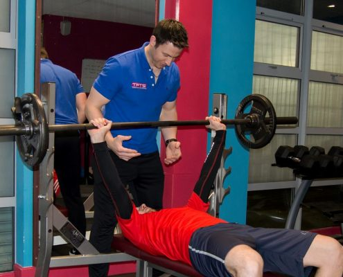 TPTS client being spotted on bench press by personal trainer darren