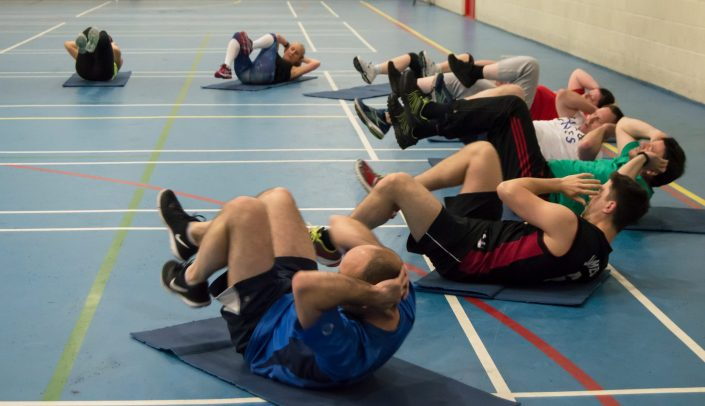 Large group of males and females doing abdominal crunches at a circuit class. Crunches are known for great body conditioning and weight loss