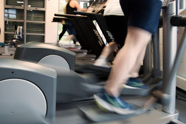 Clients using the cardio equipment inside the gym
