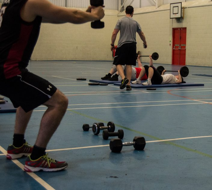 Image of multiple clients performing exercises in the sports hall of TPTS fitness club