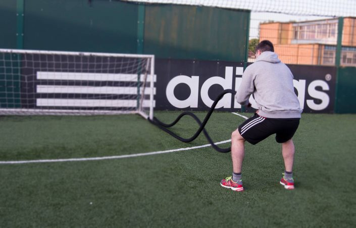 Personal Training client using the battle ropes outdoors at TPTS fitness club Swansea