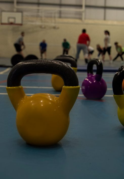 Kettle bells focused with a group of clients unfocused in background