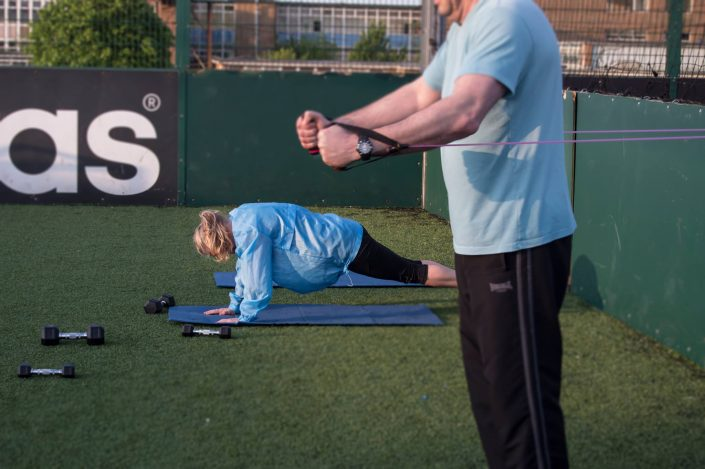 A female doing press ups and a man using the TRX ropes at a TPTS circuits class