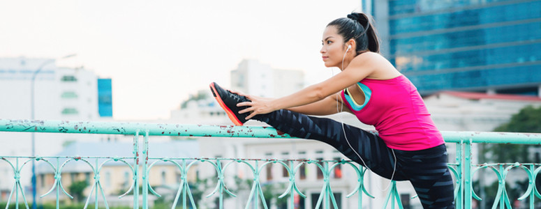 A lady wearing her fitness clothing stretching on a hand rail. The lady is also wearing earphones.