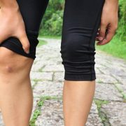 A lady holding her knee in fitness gear