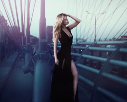 Image of a tall blonde woman in a black dress standing on a bridge with morning light